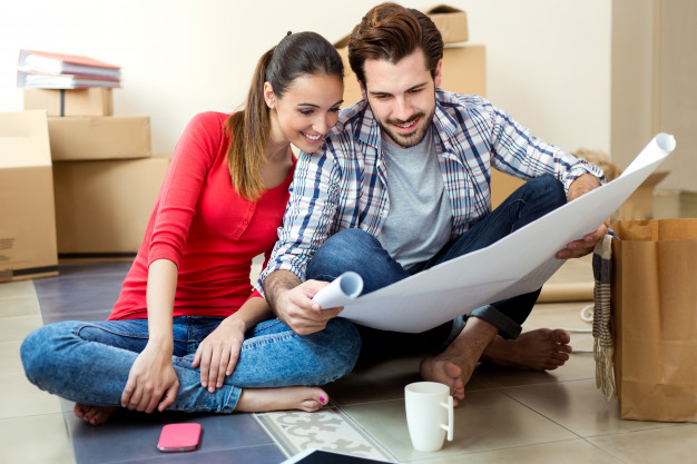 young-couple-looking-at-the-blueprints-of-their-new-home_1301-7591