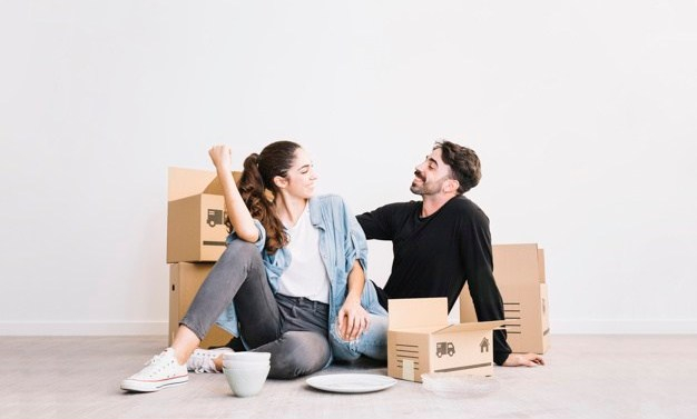 happy-couple-sitting-in-front-of-moving-boxes_23-2147703557
